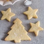christmas tree sable cut out cookie on a grey board with 3 star cookies