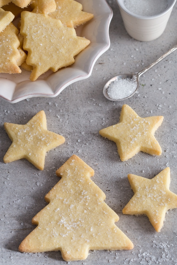 one tree and 3 stars with some cookies on a plate and a spoon of sparkling sugar on a grey board