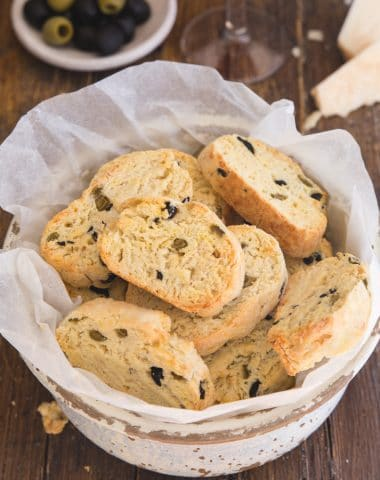 savory biscotti in a bowl with olives in a small plate and a glass of red wine