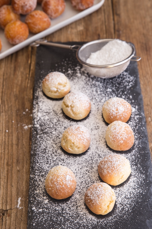 baked castagnole on a black tray dusted with powdered sugar