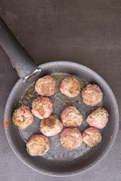 browning the meatballs in a frying pan