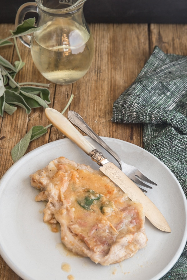 saltimbocca on a plate with a knife and fork and white wine in a jug