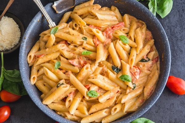 tomato pasta in a black pan with parmesan cheese in a bowl and fresh tomatoes