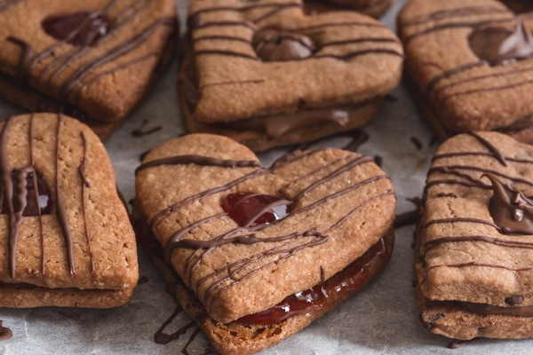 valentine sandwich cookies drizzled with chocolate on a parchment paper
