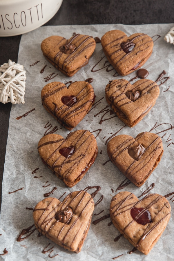 valentine cookies drizzled with chocolate on parchment paper
