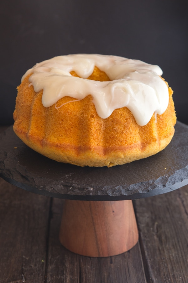 carrot cake with cream cheese frosting on a black cake stand