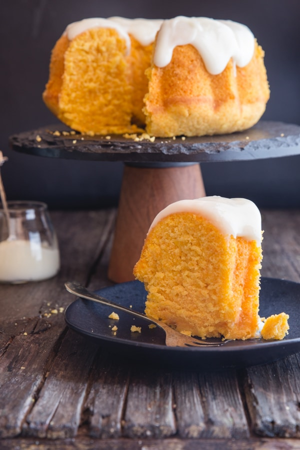 carrot cake on a black cake stand with a slice on a black plate