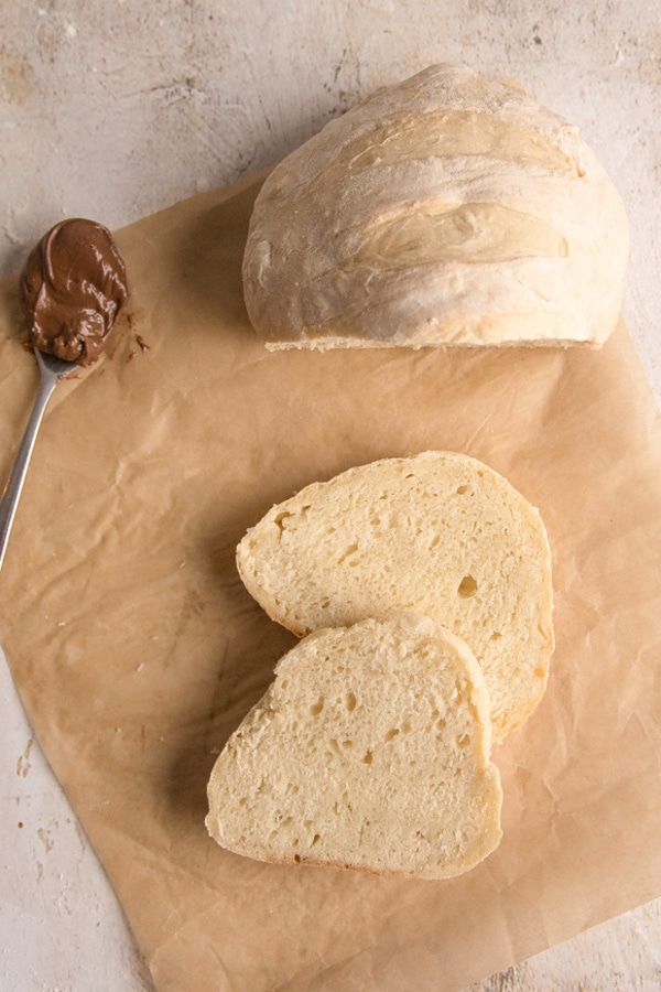 bread loaf with 2 slices cut on parchment paper with hazelnut cream on a spoon