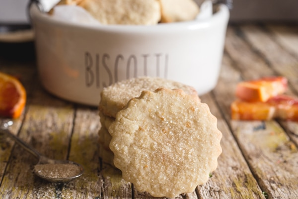 orange cookies in a white biscotti bowl and one leaning against a stack