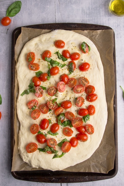 topping the dough with sliced tomatoes