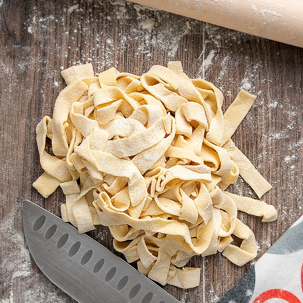2 ingredient pasta on a wooden board with a knife.