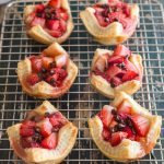 strawberry tarts on a wire rack with 3 fresh strawberries and powdered sugar