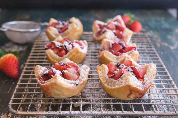 strawberry tarts sprinkled with powdered sugar on a wire rack