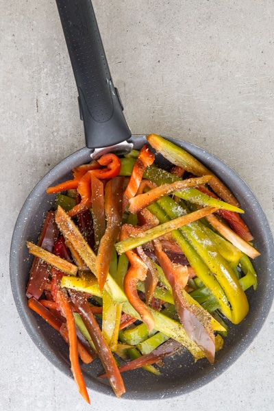 ingredients and peppers in frying pan before cooking