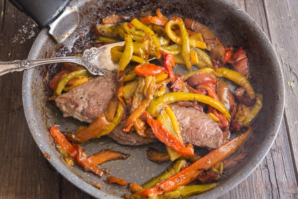 peppers and a steak in a frying pan with a fork