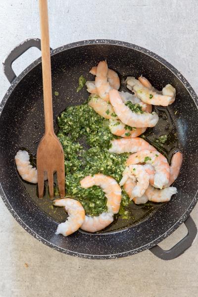 pesto, oil and shrimp in a black pan