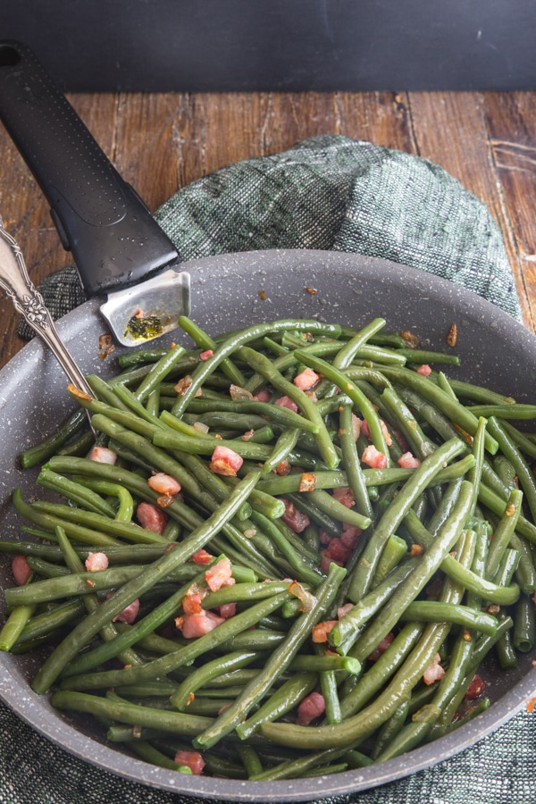 green beans & pancetta in a frying pan on a wooden board with a spoon