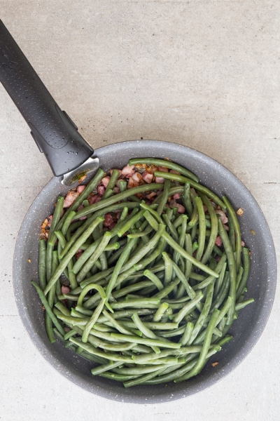 adding the green beans to the pancetta in a black pan