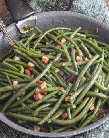 green beans & pancetta in a frying pan on a wooden board with a fork