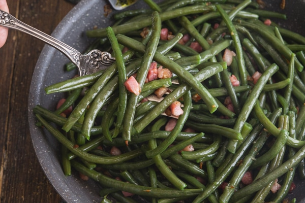 green beans & pancetta in a frying pan on a wooden board with a silver fork