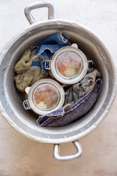 jars in a large pot with a towel wrapped around them