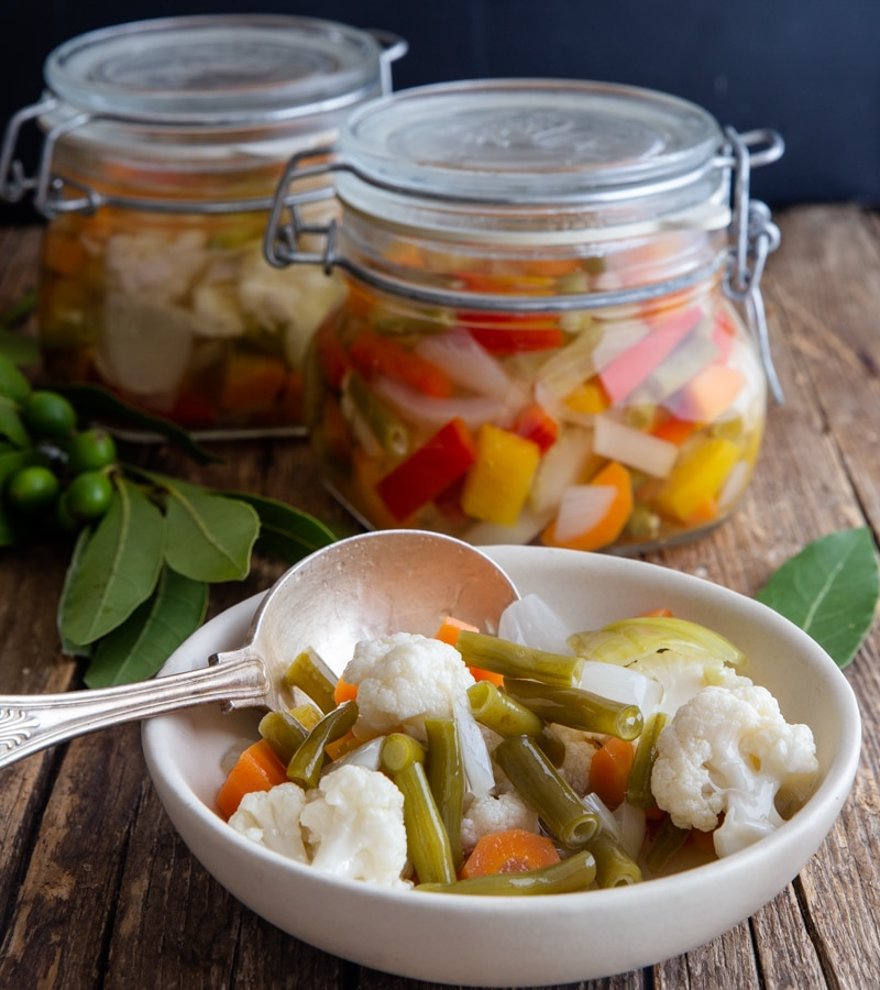 vegetables in a white bowl with a silver spoon and 2 jars full