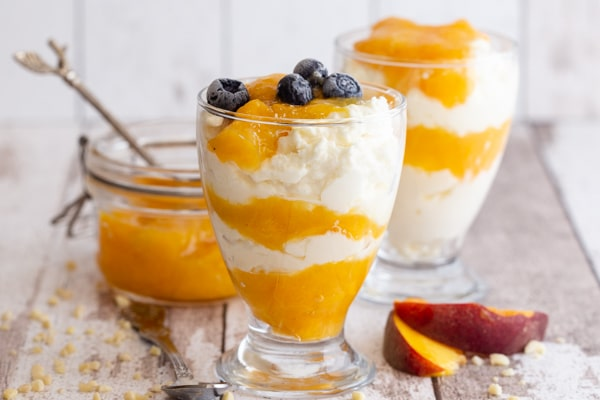 2 glasses of mousse on a white board with 2 peach slices