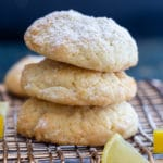 3 lemon drop cookies on a wire rack with a slice of lemon
