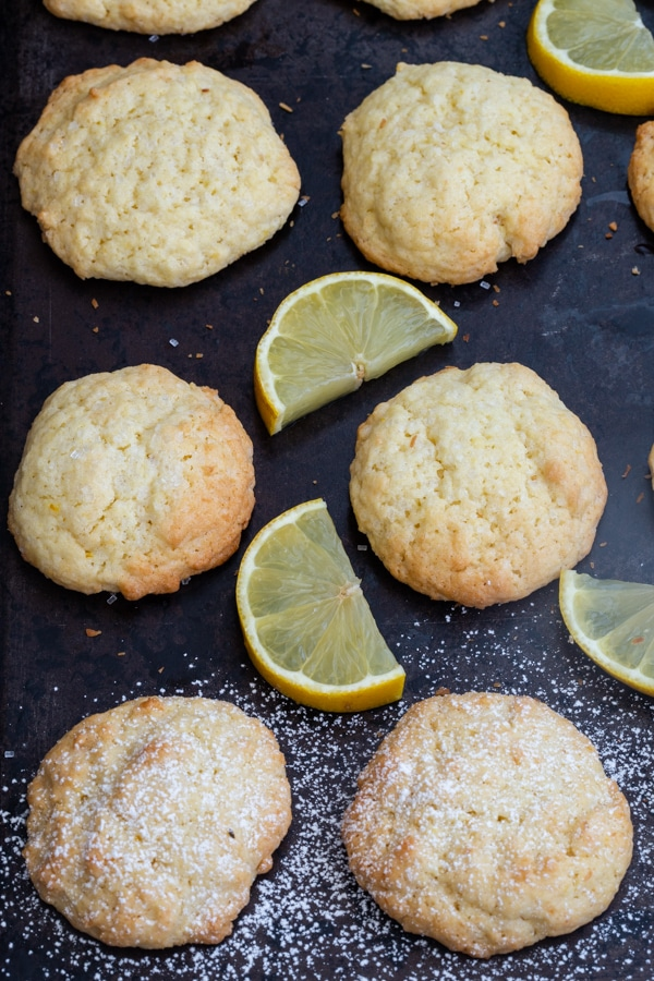 lemon cookies on a black cookie sheet with slices of lemon