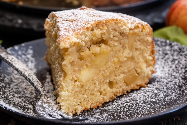 a piece of apple cake on a black plate