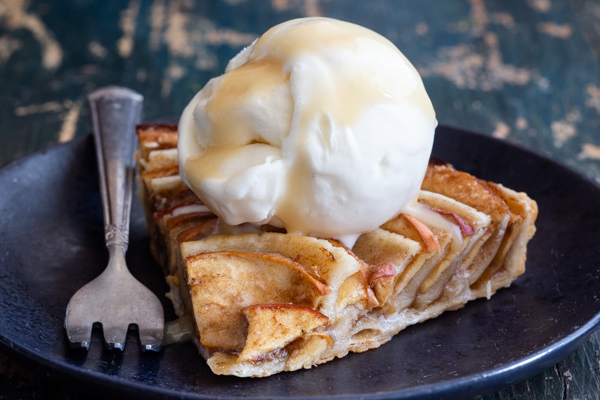 a slice of pie on a black plate with ice cream on top