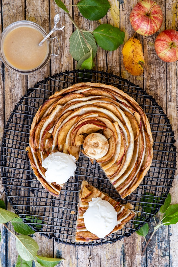 puff pastry apple pie on a black cake rack with a cut sliced and a scoop of ice cream on top