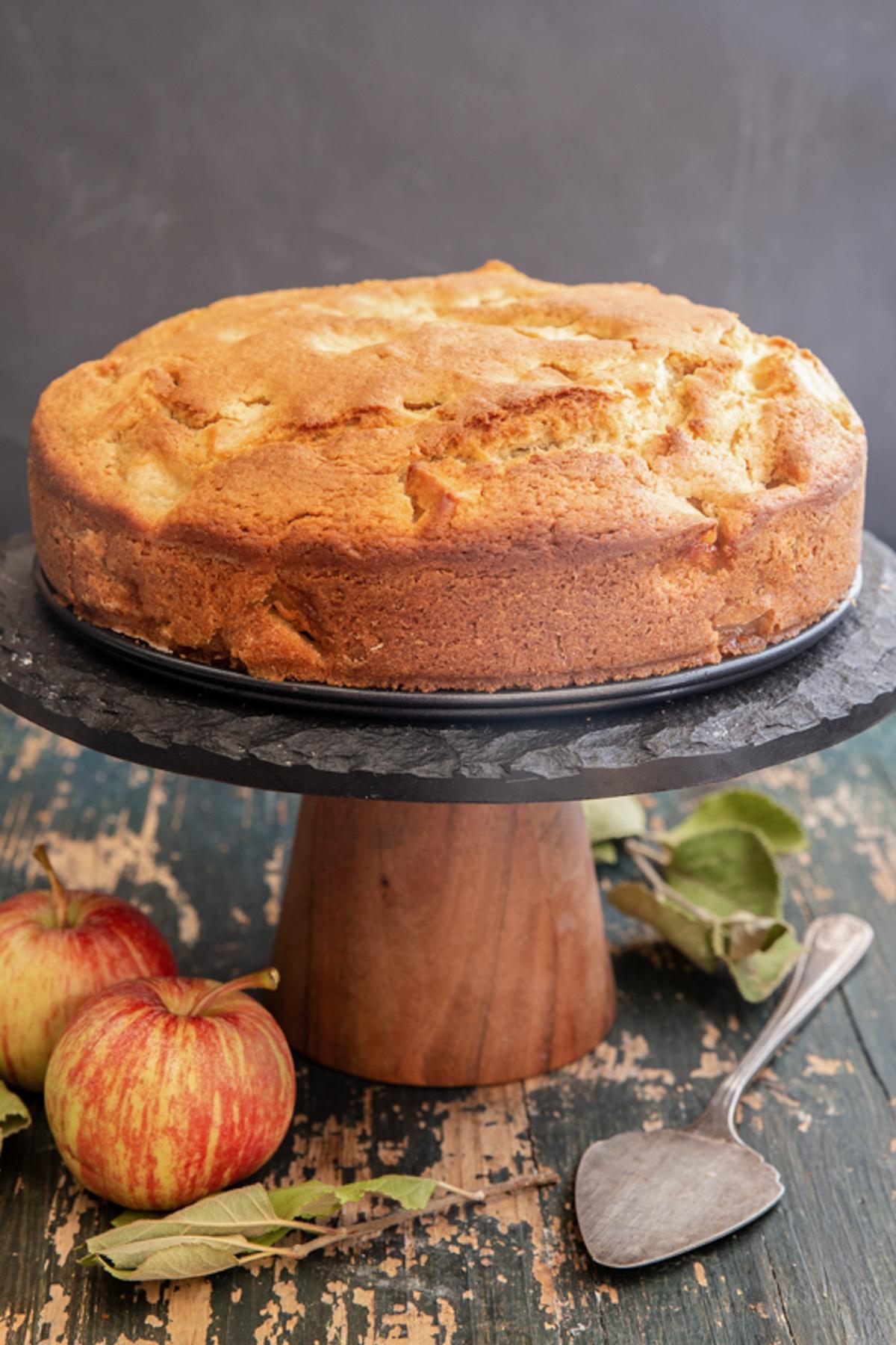 Apple cake on a black cake stand.