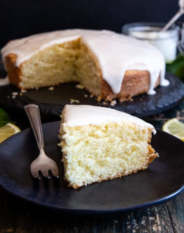 lemon yogurt cake on a black cake stand with a slice on a black plate