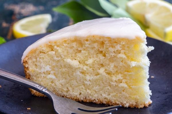 a slice of lemon cake on a black plate
