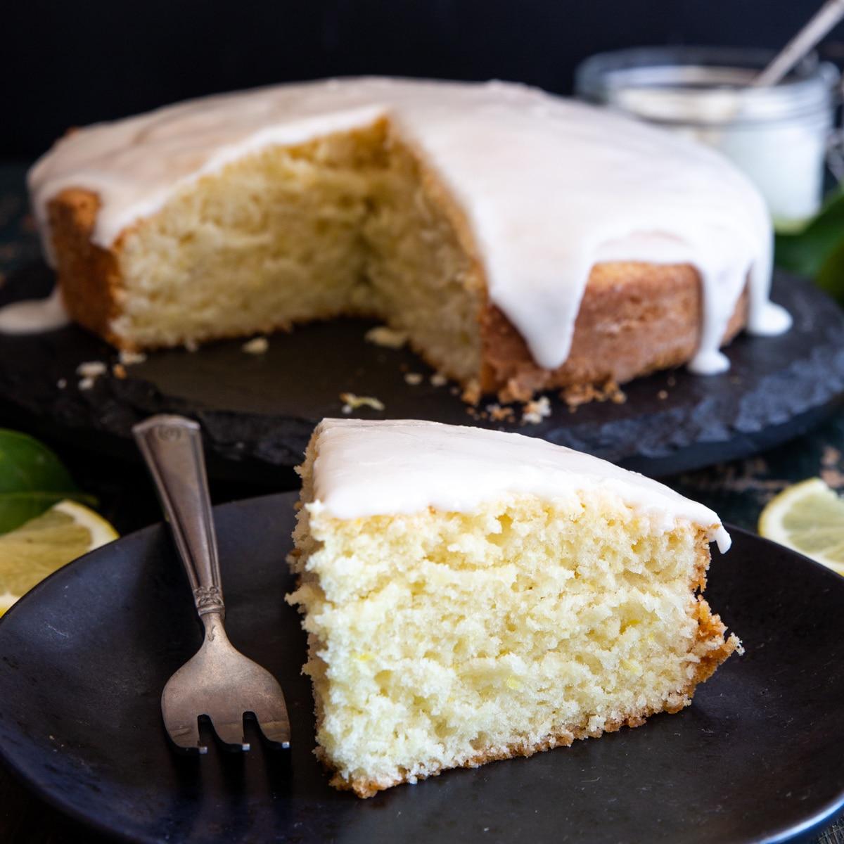 lemon yogurt cake on a black cake stand with a slice on a black plate
