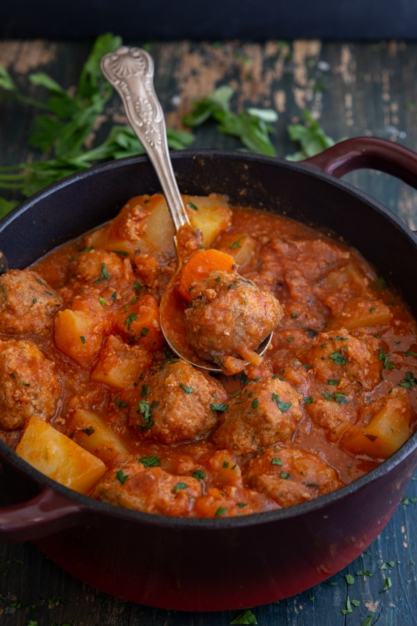 meatball stew in a red pot with a silver spoon