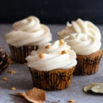 4 pumpkin cupcakes on with small stars on a grey board with 2 leaves