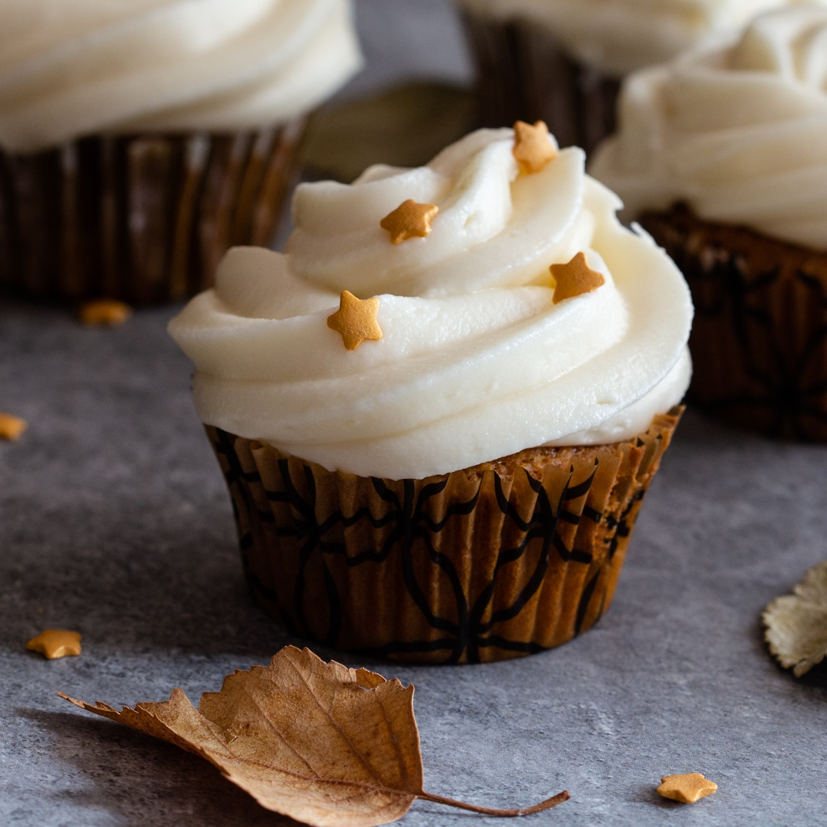 pumpkin cupcake with a leave on a grey board