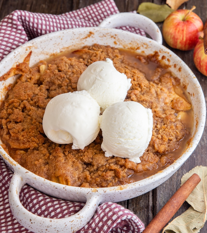 apple crisp in a white pan with 3 scoops of ice cream