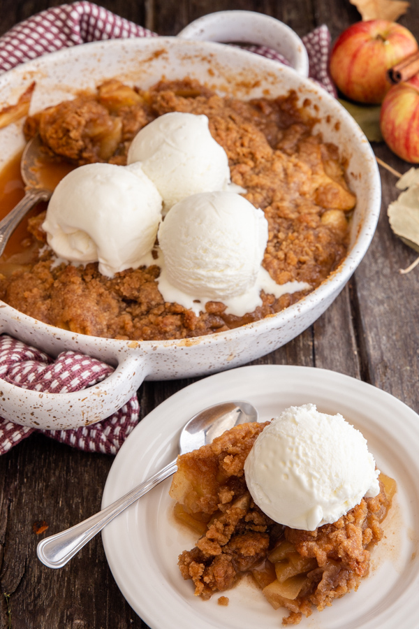 apple crisp in a white baking dish and some on a white plate