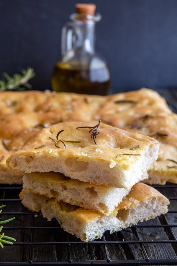 3 slices of focaccia on top of each other with remaining on a wire rack