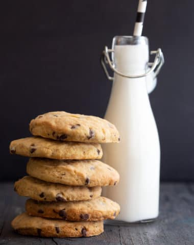 6 pumpkin cookies stacked with a bottle of milk and a straw