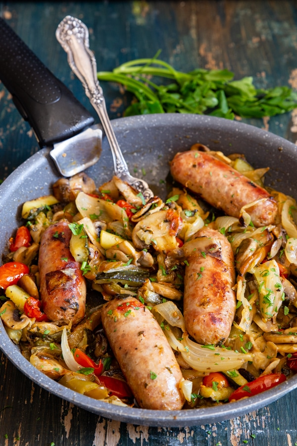 sausages and vegetables in a black pan
