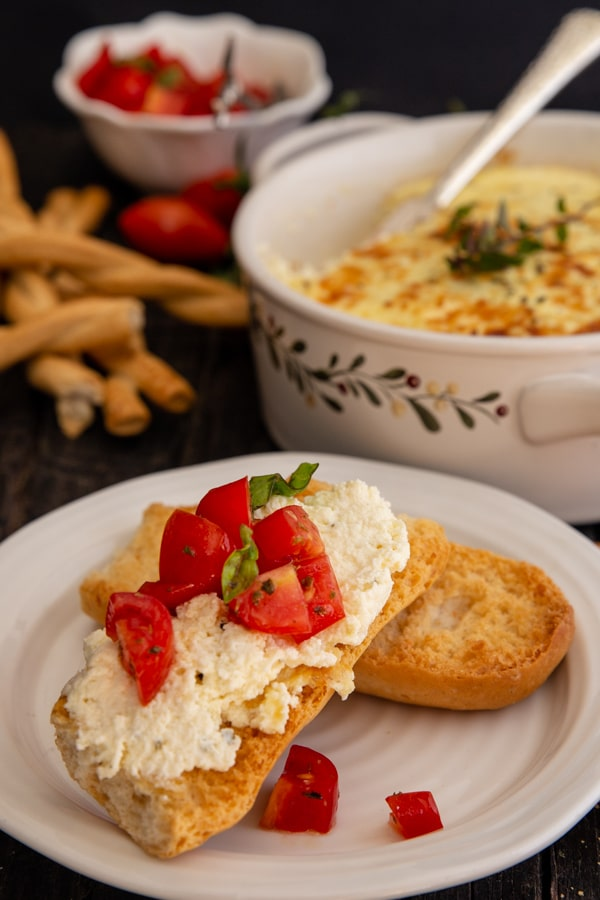 ricotta on a cracker with tomatoes and in the baking dish