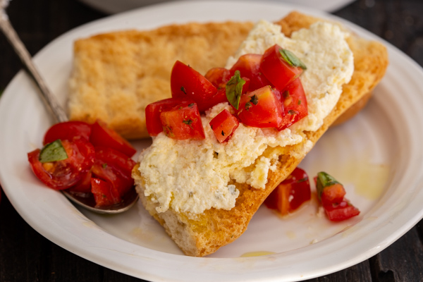 ricotta on a cracker with tossed tomatoes on top