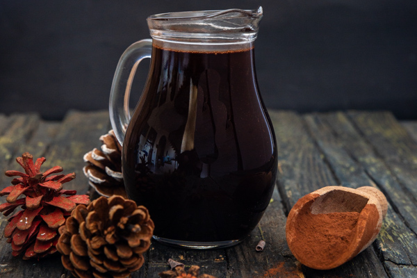 a small jug of chocolate syrup with a scoop of cocoa