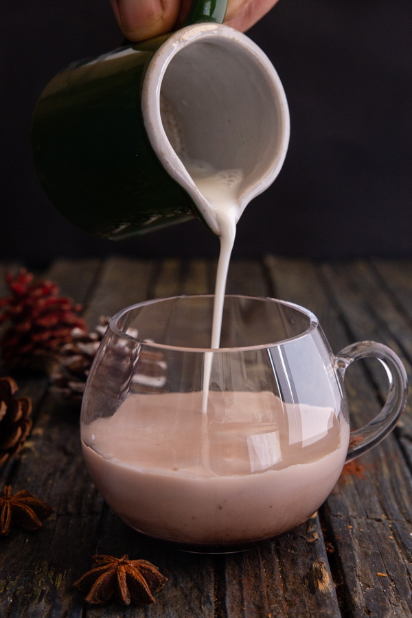 pouring milk into a cup of chocolate