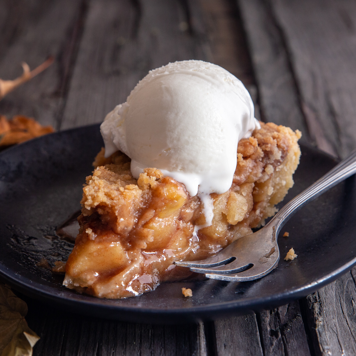 a slice of apple pie with ice cream on a black plate