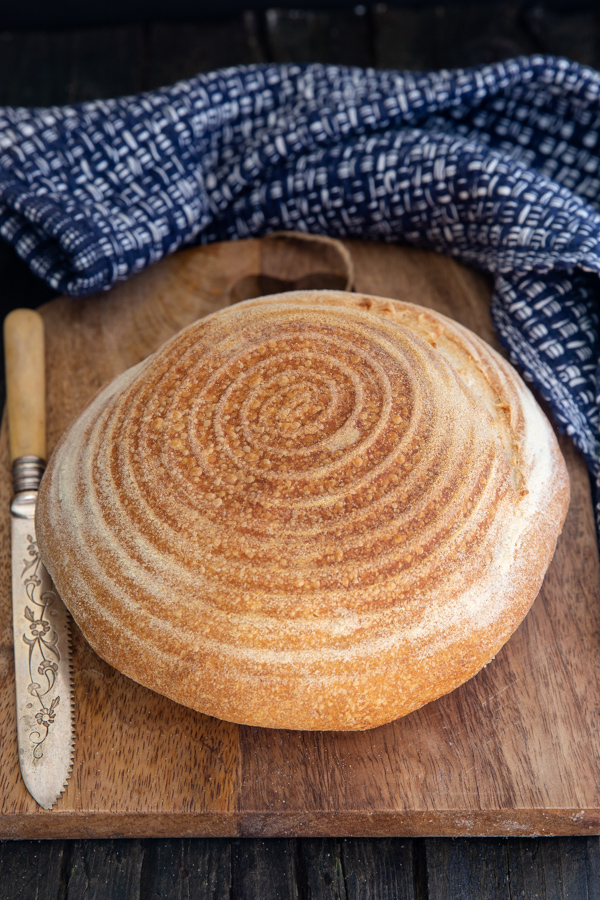 loaf of sour dough bread on a wooden board